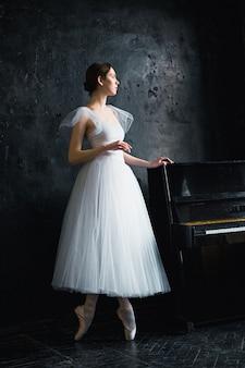 Jonge en ongelooflijk mooie ballerina poseert in een zwarte studio