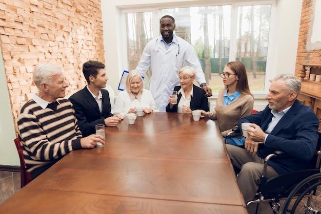 Jonge en oude mensen zitten samen aan de tafel in de kamer.