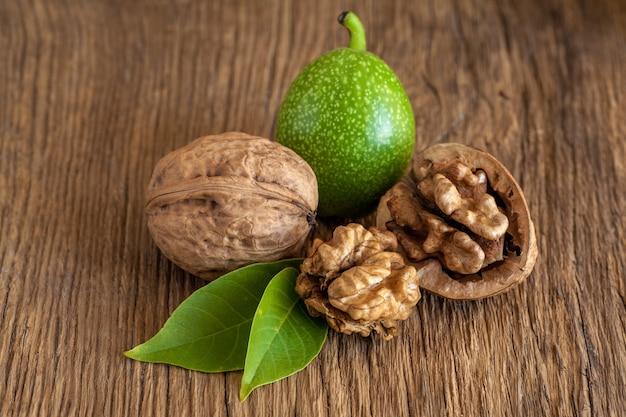 Jonge en oude walnoten op houten tafel.