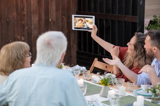 Jonge en oudere stellen communiceren met hun vrienden of familieleden in videochat