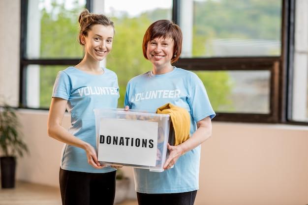 Jonge en oudere vrijwilligers gekleed in blauwe t-shirts met container met donaties van kleding binnenshuis op kantoor