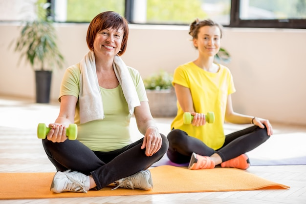 Jonge en oudere vrouw in sportkleding zittend tijdens de yoga-training binnenshuis