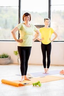 Jonge en oudere vrouwen in sportkleding doen samen yoga binnenshuis, thuis of in de sportschool