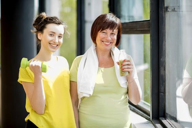 Jonge en oudere vrouwen in sportkleding trainen met halters binnenshuis op de achtergrond van het raam