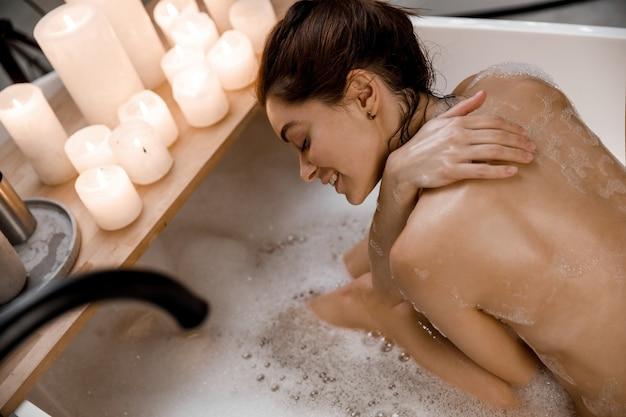 Jonge en rustige vrouw ontspannen in het prachtige vintage bad vol schuim in de retro badkamer versierd met kaarsen close-up. gezonde behandeling en plezier.