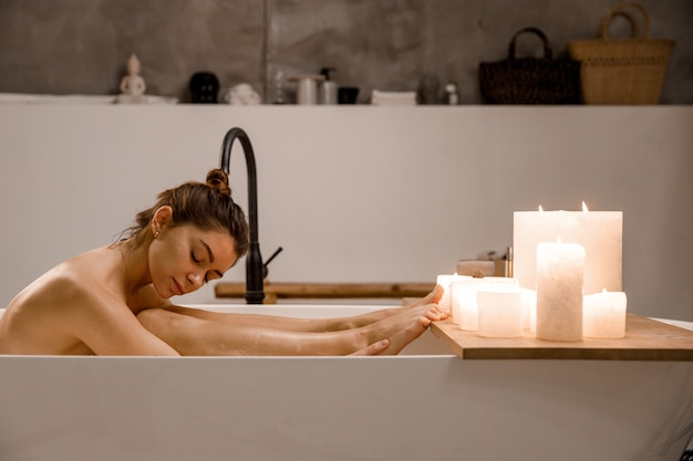 Jonge en rustige vrouw ontspannen in het prachtige vintage bad vol schuim in de retro badkamer versierd met kaarsen. gezonde behandeling en plezier