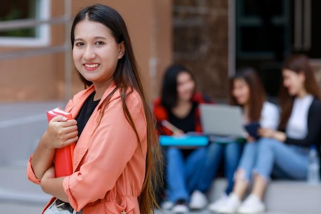 Jonge en schattige aziatische studentmeisjes die boeken vasthouden, poseren voor de camera met een groep vrienden die op de achtergrond vervagen voor het schoolgebouw. leren en vriendschap van tieners goede vriend concept.