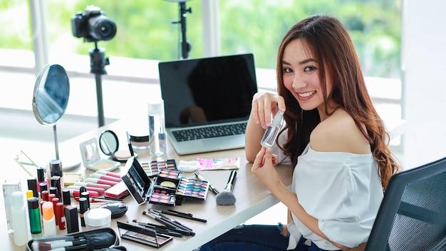 Jonge en schattige aziatische vrouwelijke vlogger, influencer of online verkoper die zit met cosmeticaproducten en dslr-camera en laptop-notebookcomputer klaar om online livestream uit te zenden of video op te nemen.