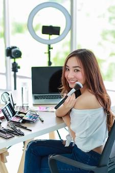 Jonge en schattige aziatische vrouwelijke vlogger, influencer of online verkoper die zit met cosmeticaproducten en dslr-camera en smartphone en laptop-notebookcomputer klaar om video-livestream uit te zenden.