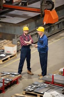 Jonge en senior ingenieurs of technici in beschermende helmen en uniform staan in opslagruimte en advies