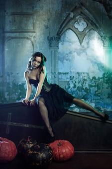 Jonge en sexy vrouw, beeld van heksen in een begraafplaatszitting op dekselkist.