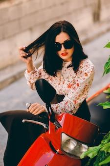 Jonge en sexy vrouw met haar scooter