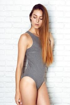 Jonge en sexy vrouwen die zich in erotische zwempakken stellen