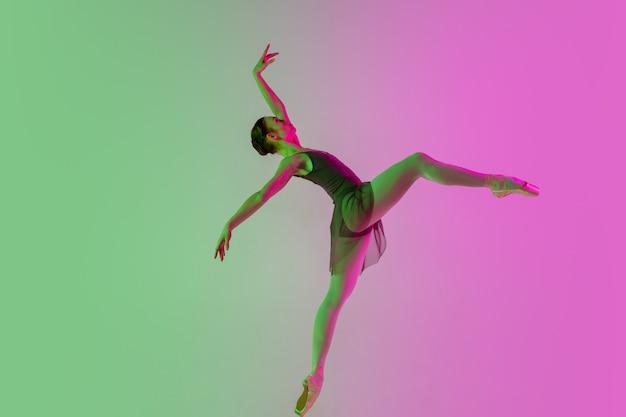 Jonge en sierlijke balletdanser geïsoleerd op gradiënt roze groene studio achtergrond