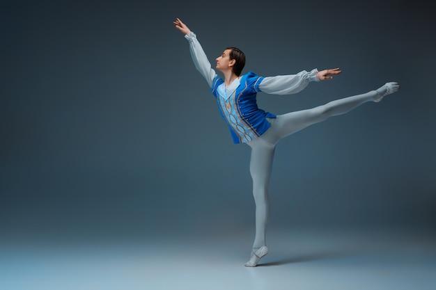 Jonge en sierlijke balletdanser in actie geïsoleerd op studio achtergrond