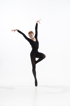 Jonge en sierlijke balletdanser in minimale zwarte stijl geïsoleerd op wit