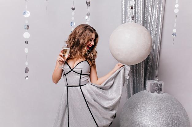 Jonge en slimme vrouw, in chique bui, verheugt zich en heeft plezier met nieuwjaarsspeelgoed en tilt haar chique nieuwjaarsjurk op