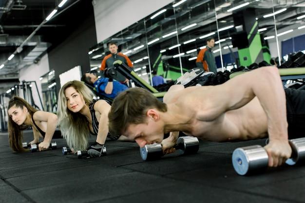 Jonge en sportieve man bank doen push-ups met halters samen met twee mooie vrouwen in de sportschool