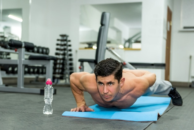 Jonge en sportieve man plank oefening in de sportschool doet