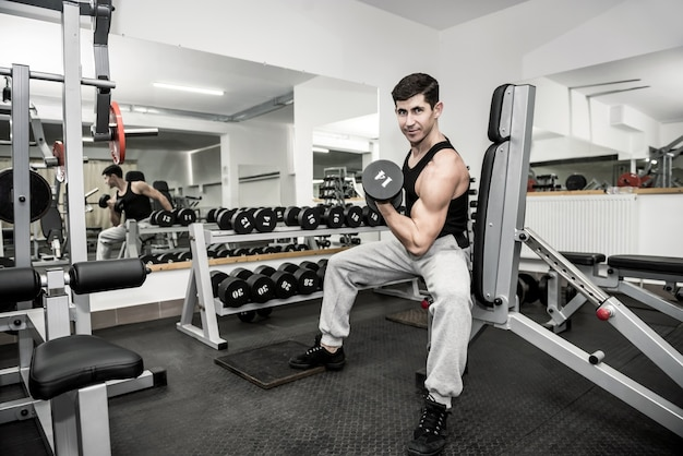 Jonge en sportieve man training in de sportschool