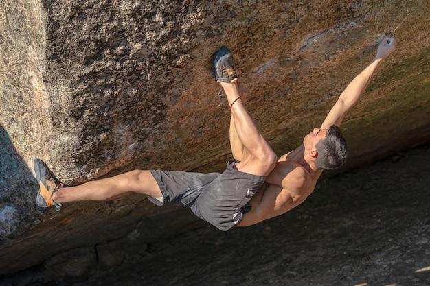 Jonge en sterke klimmer doet rotsklimmen