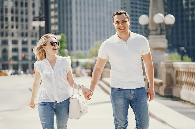 Jonge en stijlvolle geliefden paar in witte t-shirts en spijkerbroek wandelen in een grote stad