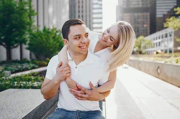 Jonge en stijlvolle geliefden paar in witte t-shirts en spijkerbroek zitten in een grote stad