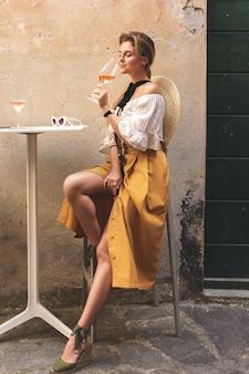 Jonge en stijlvolle vrouw drinkt rose wijn in de straatbar
