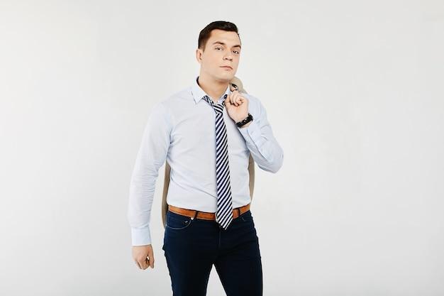 Jonge en stijlvolle zakenman in het witte overhemd met een gestreepte stropdas en in de donkere spijkerbroek met een beige blazer