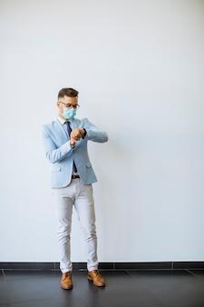 Jonge en stijlvolle zakenman met gezichtsmasker staat bij de muur op kantoor en controleert de tijd op het horloge
