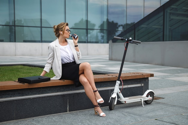 Jonge en stijlvolle zakenvrouw roken vape na haar werk