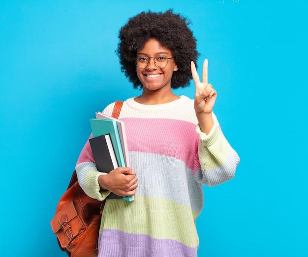 Jonge en student afro vrouw die vriendelijk glimlacht kijkt, nummer twee of seconde met vooruit hand toont, aftellend