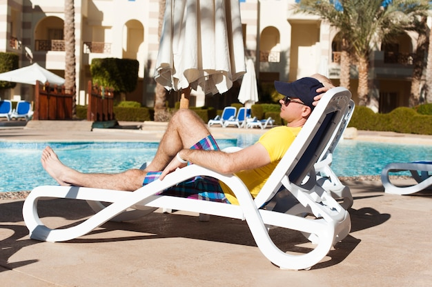 Jonge en succesvolle man liggend op een ligstoel in het hotel in de buurt van zwembad zweten