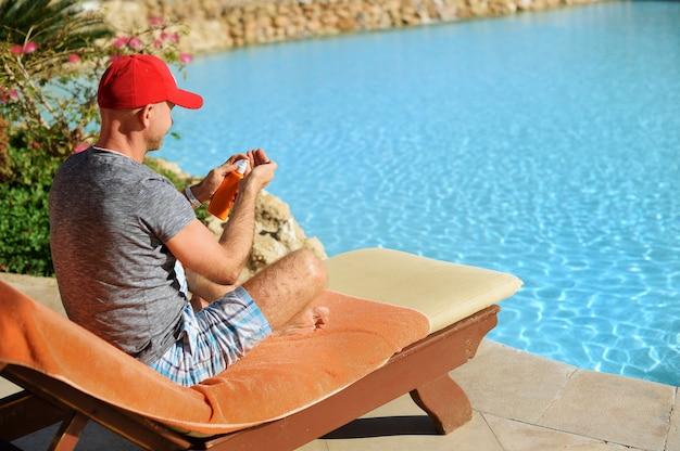 Jonge en succesvolle man op een ligstoel perst sunblock crème uit een buis