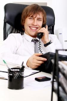 Jonge en succesvolle zakenman die telefonisch spreekt