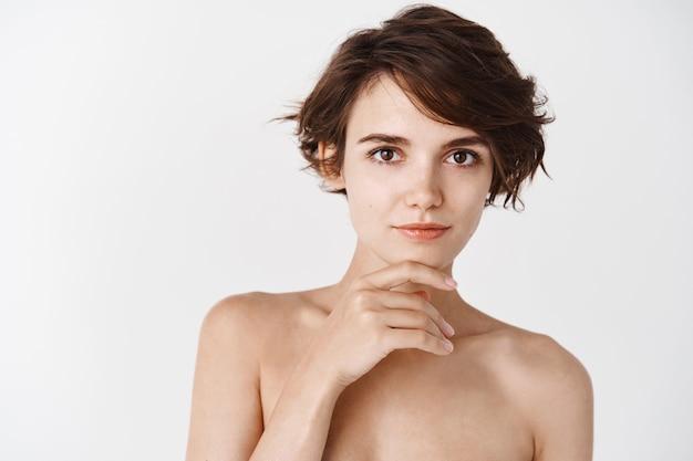 Jonge en tedere vrouw zonder make-up, gehydrateerde en gehydrateerde schone huid, kin aanraken en glimlachend naakt over witte muur staan