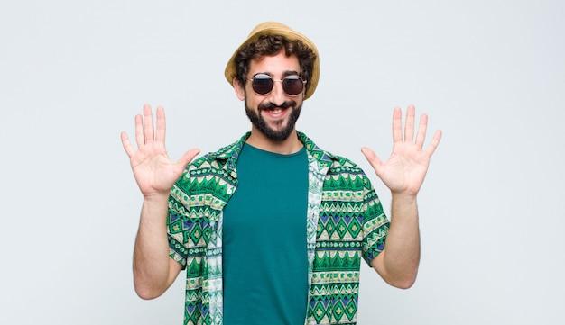 Jonge en toeristenmens die vriendelijk glimlacht kijkt, nummer tien of tiende met vooruit hand toont, aftellend op witte muur