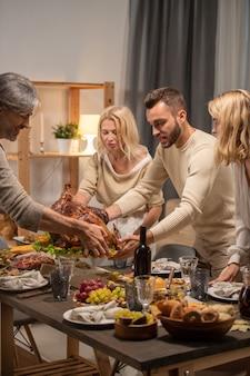 Jonge en volwassen mannen houden een dienblad met zelfgemaakte geroosterde kalkoen vast en zetten het op een feestelijke tafel tussen drankjes, vers fruit en desserts