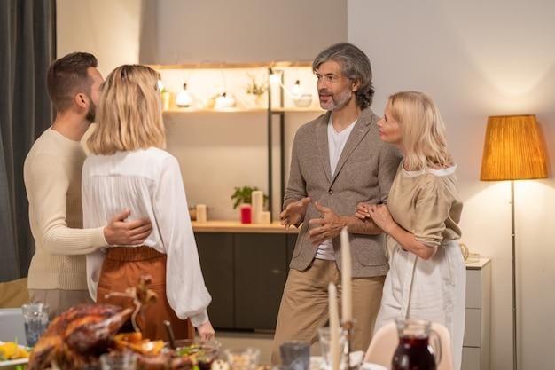 Jonge en volwassen stellen die nieuws bespreken terwijl ze voor elkaar staan door een feestelijke tafel te serveren tegen het interieur van de gang of keuken