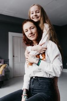 Jonge en volwassen zussen omhelzen elkaar op het hok, wat staat voor vriendschap, vertrouwen, gelijkenis