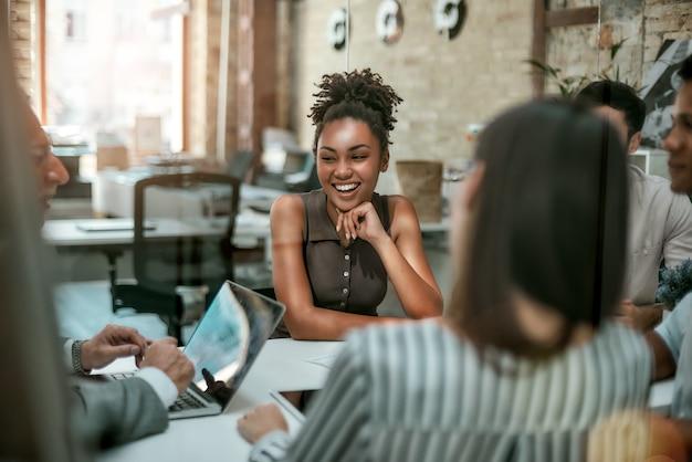 Jonge en vrolijke afro-amerikaanse vrouw die lacht tijdens een ontmoeting met collega's