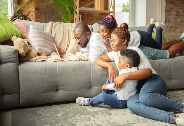 Jonge en vrolijke familie tijdens quarantaine, isolatie tijd samen doorbrengen thuis.