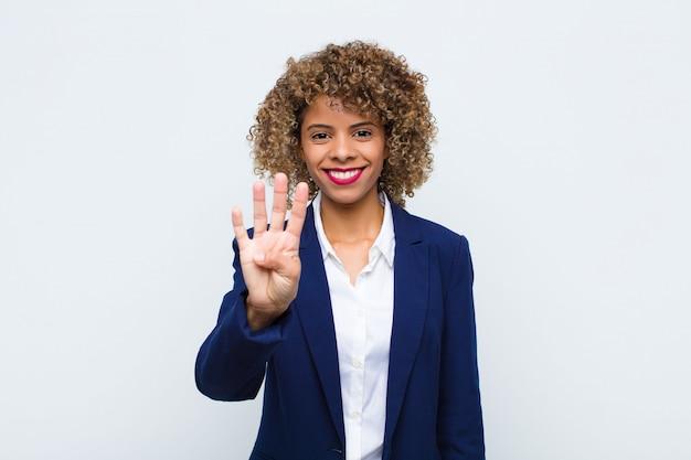 Jonge en vrouw die afro-amerikaanse vriendschappelijk glimlachen kijken, tonend nummer vier of vierde met voorwaartse hand, aftellend tegen vlakke muur