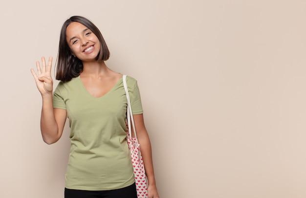 Jonge en vrouw die vriendelijk glimlacht kijkt, nummer vier of vierde met vooruit hand toont, aftellend