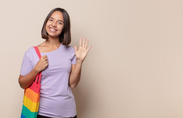 Jonge en vrouw die vriendelijk glimlacht kijkt, nummer vijf of vijfde met vooruit hand toont, aftellend