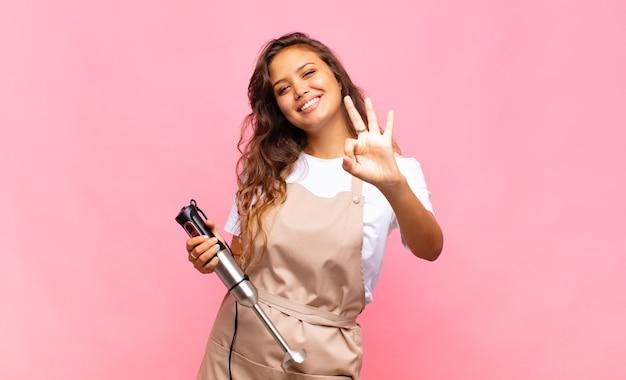 Jonge en vrouwenbakker die vriendelijk glimlacht kijkt, nummer drie of derde met vooruit hand toont, aftellend
