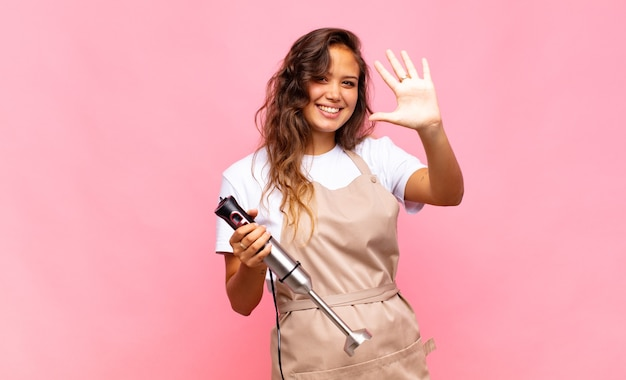 Jonge en vrouwenbakker die vriendelijk glimlacht kijkt, nummer vijf of vijfde met vooruit hand toont