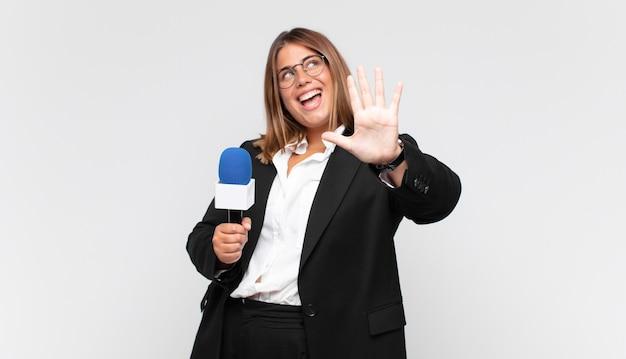 Jonge en vrouwenverslaggever die vriendelijk glimlacht kijkt, nummer vijf of vijfde met vooruit hand toont, aftellend