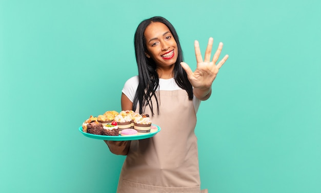 Jonge en zwarte vrouw die vriendelijk glimlacht kijkt, nummer vijf of vijfde met vooruit hand toont, aftellend. bakkerij chef-kok concept