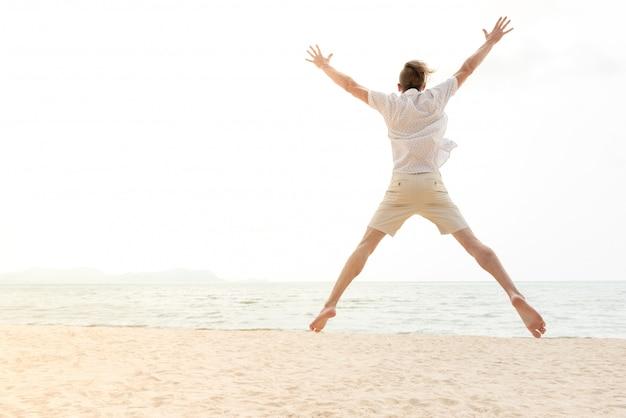 Jonge energieke gelukkige toeristenmens die bij het strand springt